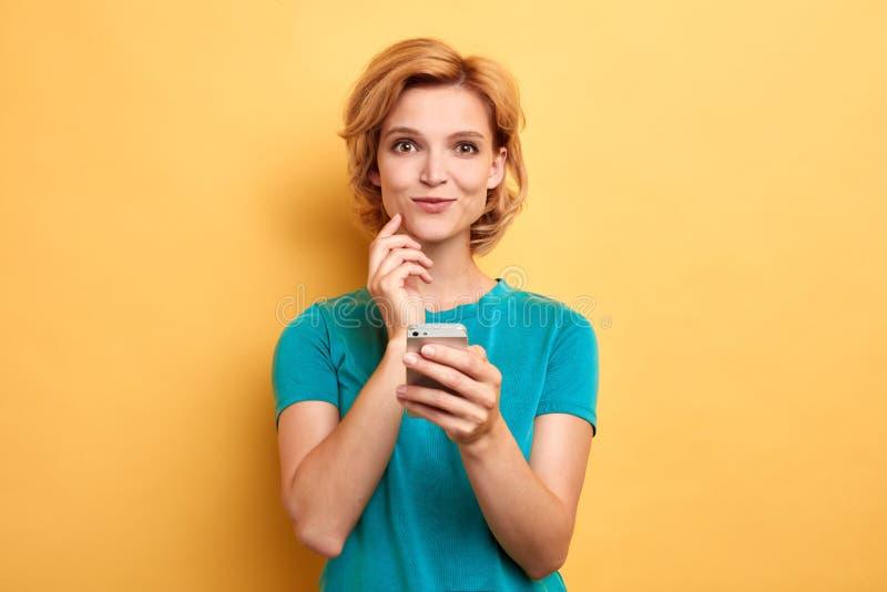 Glimlachend vrolijk meisje die omhoog tot een bericht maken aan haar vriend stock foto