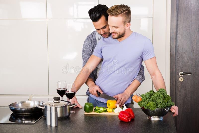 glimlachend vrolijk paar die voedsel voorbereiden royalty-vrije stock afbeeldingen