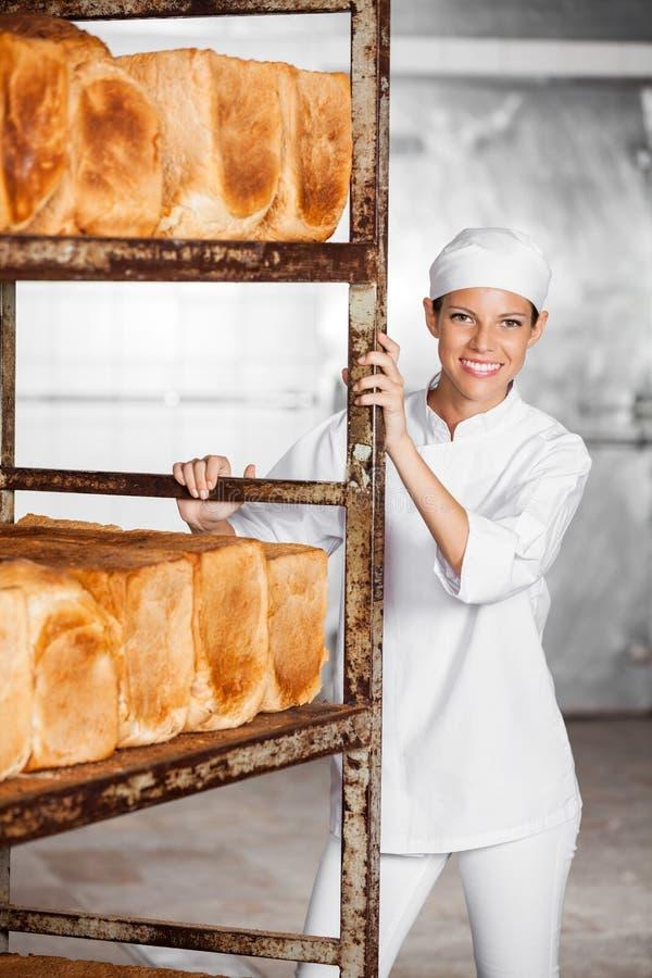 Glimlachend Vrouwelijk Baker Pushing Rack With vers royalty-vrije stock foto