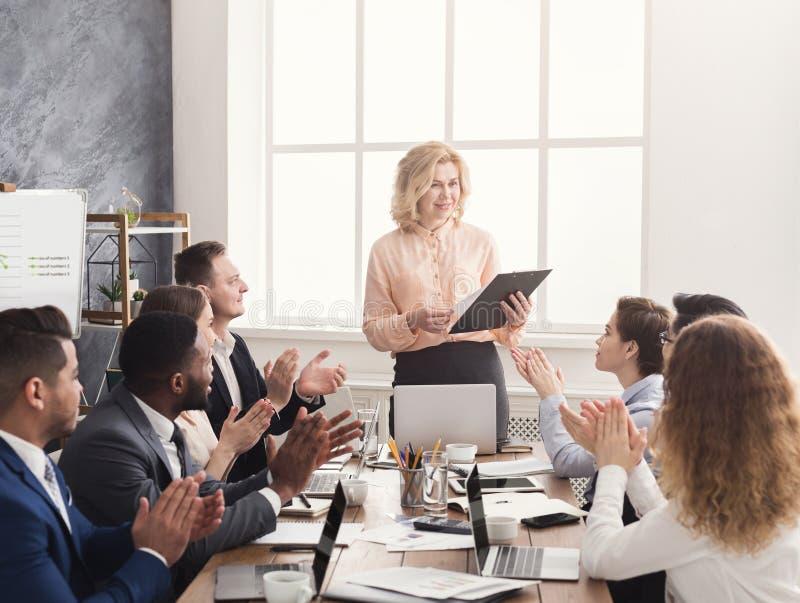Glimlachend vrouwelijk werkgever en team die handen slaan op vergadering royalty-vrije stock foto