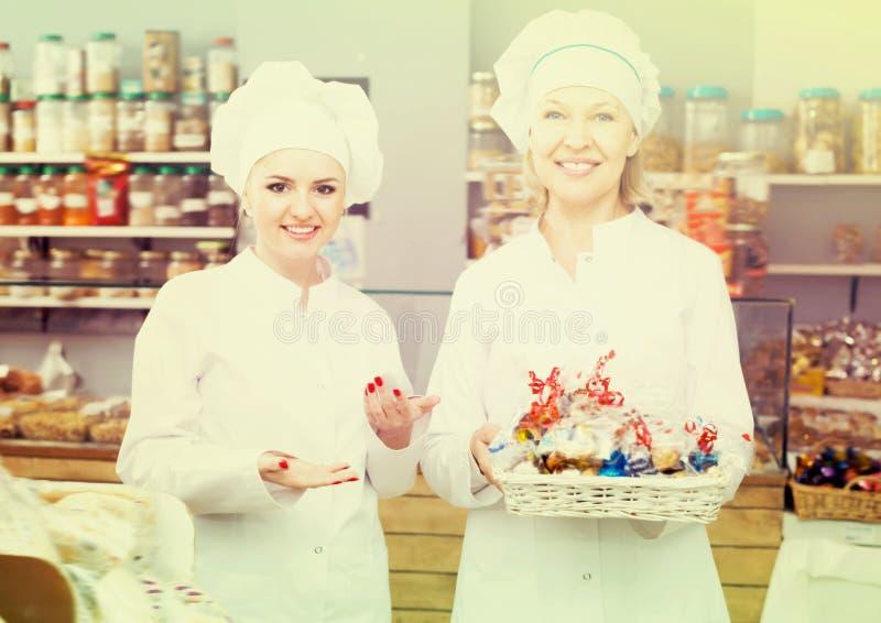 Glimlachend vrouwenpersoneel die snoepjes aanbieden stock foto