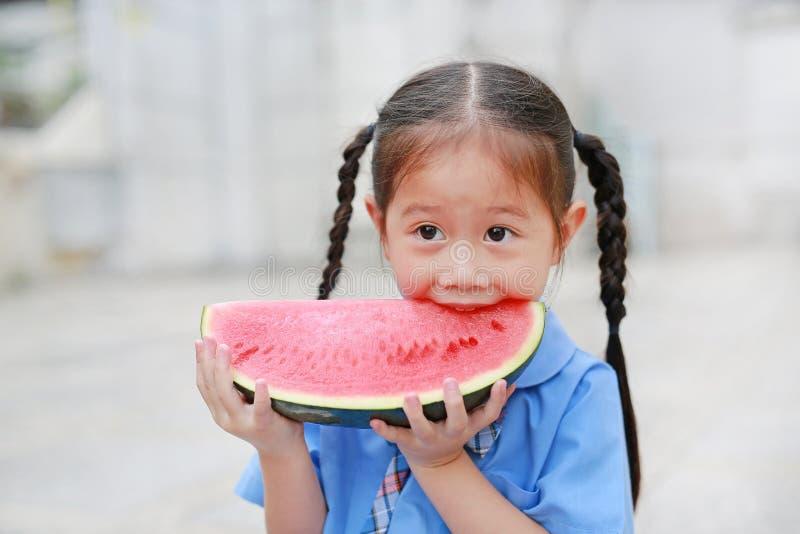 Glimlachend weinig Aziatisch kindmeisje in eenvormige school geniet in openlucht het eten van watermeloen stock fotografie