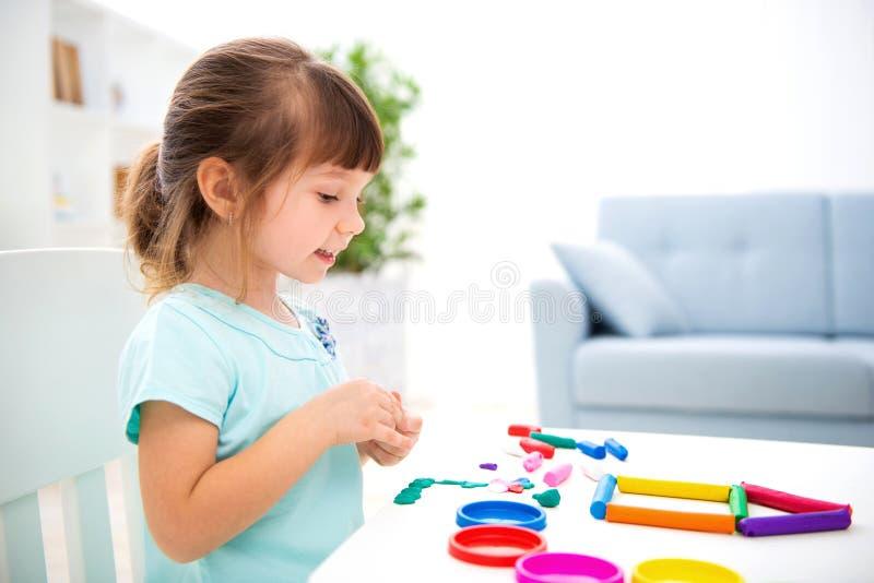 Glimlachend weinig mooi meisje beeldhouw nieuw huis van plasticine Kinderencreativiteit Gelukkige kinderjaren Inwijdingsfeestdrom stock foto's