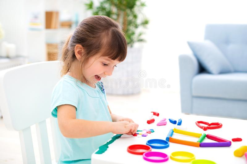 Glimlachend weinig mooi meisje beeldhouw nieuw huis van plasticine Kinderencreativiteit Gelukkige kinderjaren Inwijdingsfeestdrom royalty-vrije stock fotografie