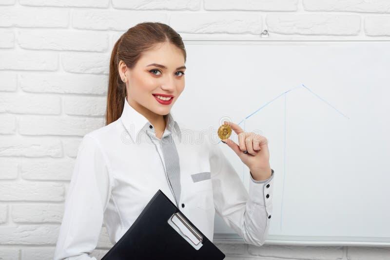 Glimlachend wijfje in witte slimme cryptocurrency van de blouseholding bitcoin dichtbij witte presentatieraad royalty-vrije stock afbeeldingen