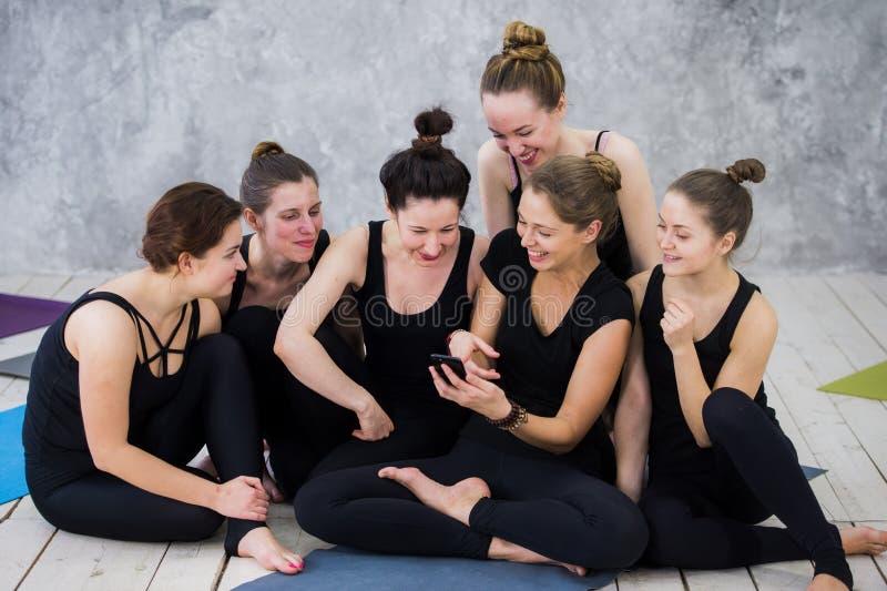 Glimlachend yogimeisje die, hebbend een onderbreking bij klasse, groep vrienden die op de telefoon letten op uitoefenen royalty-vrije stock foto's