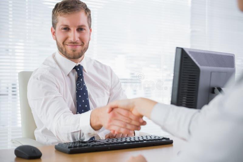 Glimlachend zakenman het schudden handen met een mede arbeider en het kijken a stock fotografie