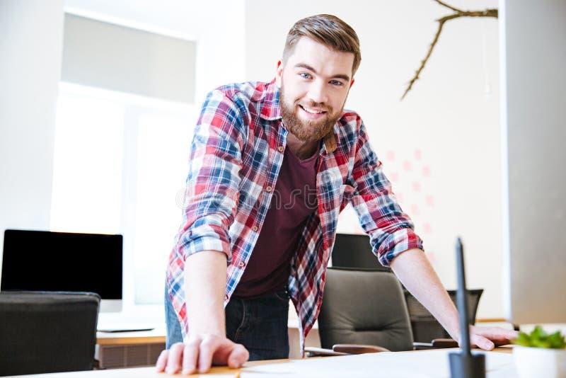 Glimlachend zeker jong mannetje met baard die zich in bureau bevinden stock afbeelding