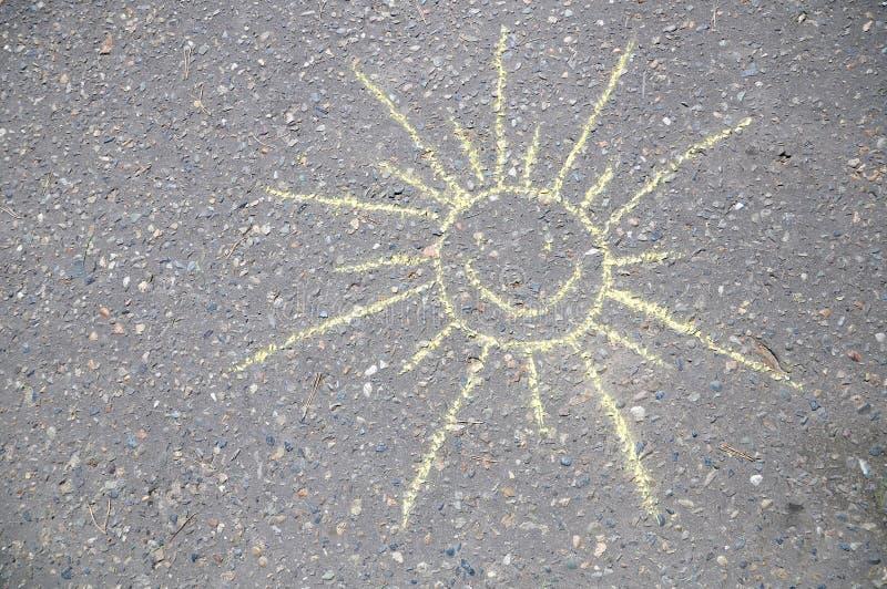 Glimlachend zon met gezicht door krijt op asfalt, smileyteken wordt openlucht door kinderen wordt geschetst geschilderd dat terwi royalty-vrije stock afbeelding