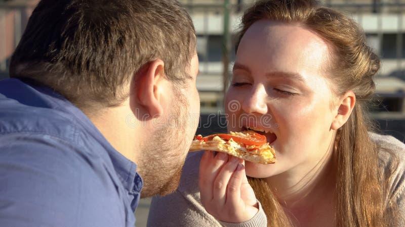 Glimlachend zwaarlijvig paar die pizza van smaak, voedselhartstocht, bovenmatig gewichtsprobleem genieten royalty-vrije stock afbeelding