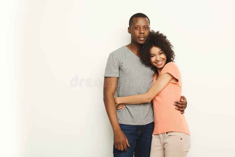 Glimlachend zwart paar in het toevallige omhelzen bij witte studioachtergrond stock afbeelding