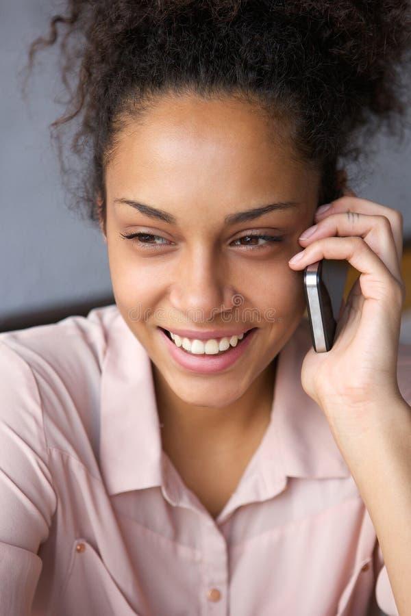Glimlachend zwarte die op celtelefoon spreken royalty-vrije stock foto