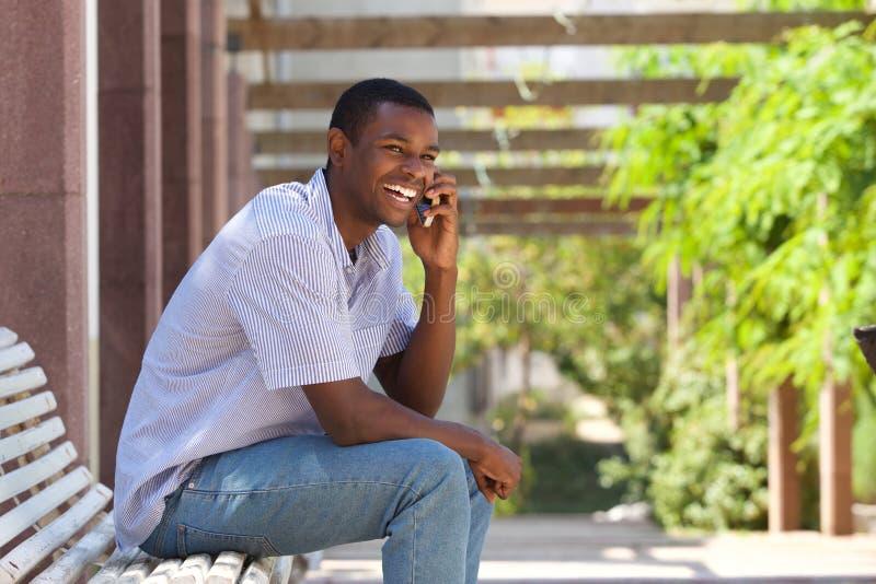 Glimlachend zwarte kerel die op mobiele telefoon buiten spreken royalty-vrije stock afbeelding