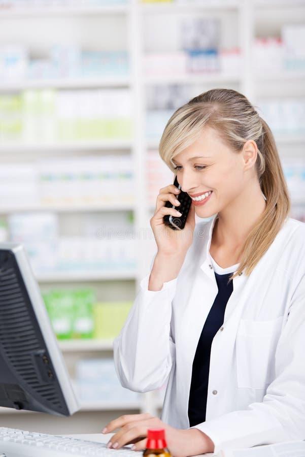 Glimlachende aantrekkelijke apotheker die bij de telefoon spreken royalty-vrije stock foto's