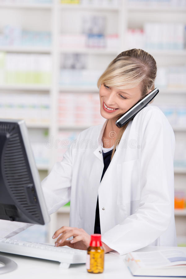 Glimlachende aantrekkelijke apotheker die bij de telefoon spreken stock afbeelding