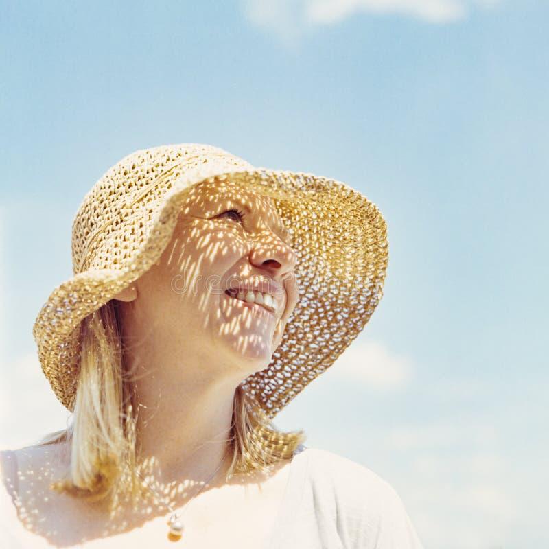 Glimlachende aantrekkelijke blondevrouw met de zomerhoed die zich voor een blauwe hemel bevinden Portretschot op film De zomer, v stock foto