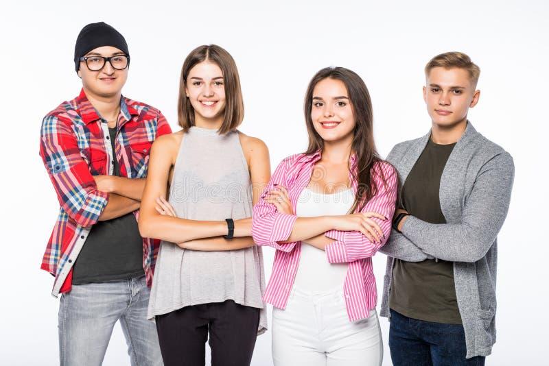 Glimlachende aantrekkelijke groep jongeren die zich met gekruiste wapens bevinden, tegen witte achtergrond royalty-vrije stock foto's