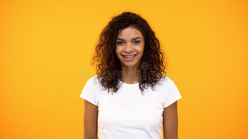 Glimlachende aantrekkelijke jonge vrouw die camera op oranje achtergrond, schoonheid kijken stock afbeelding