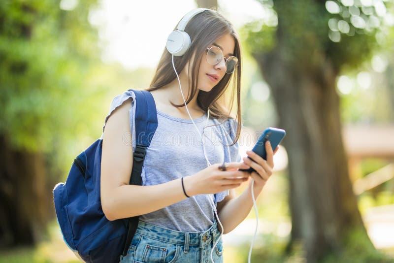 Glimlachende aantrekkelijke jonge vrouw die met rugzak aan muziek van telefoon in park luisteren royalty-vrije stock foto