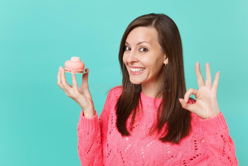 Glimlachende aantrekkelijke jonge vrouw in gebreide roze sweater die O.K. gebaar tonen die in hand cake houden die op blauw wordt stock foto's