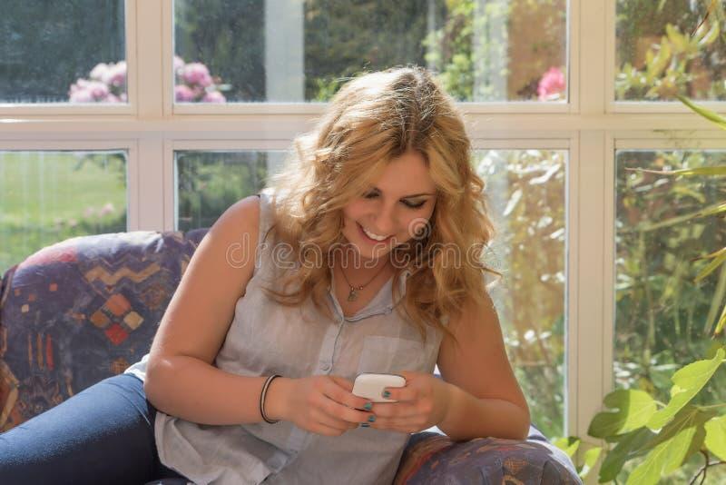 Glimlachende aantrekkelijke jonge vrouw met slimme telefoon royalty-vrije stock fotografie