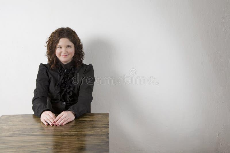 Glimlachende aantrekkelijke jonge vrouw in zwart overhemd stock foto