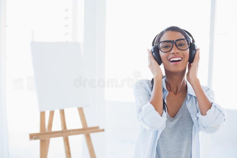 Glimlachende aantrekkelijke kunstenaar die aan muziek luisteren royalty-vrije stock afbeelding