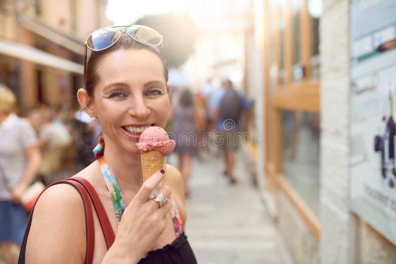 Glimlachende aantrekkelijke modieuze vrouw die van roomijs genieten royalty-vrije stock afbeeldingen