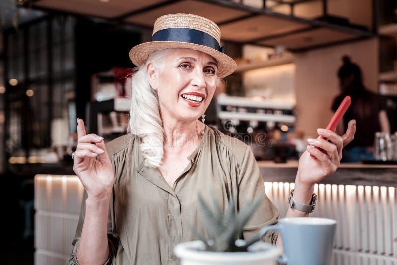 Glimlachende aantrekkelijke oude vrouw die strohoed op haar hoofd dragen royalty-vrije stock foto's