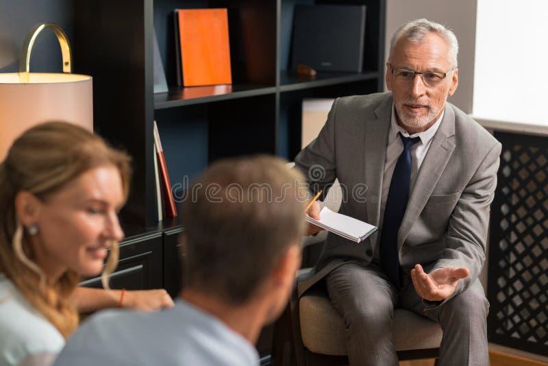 Glimlachende aantrekkelijke psychoanaliticus die aan zijn mannelijke patiënt spreken royalty-vrije stock afbeelding