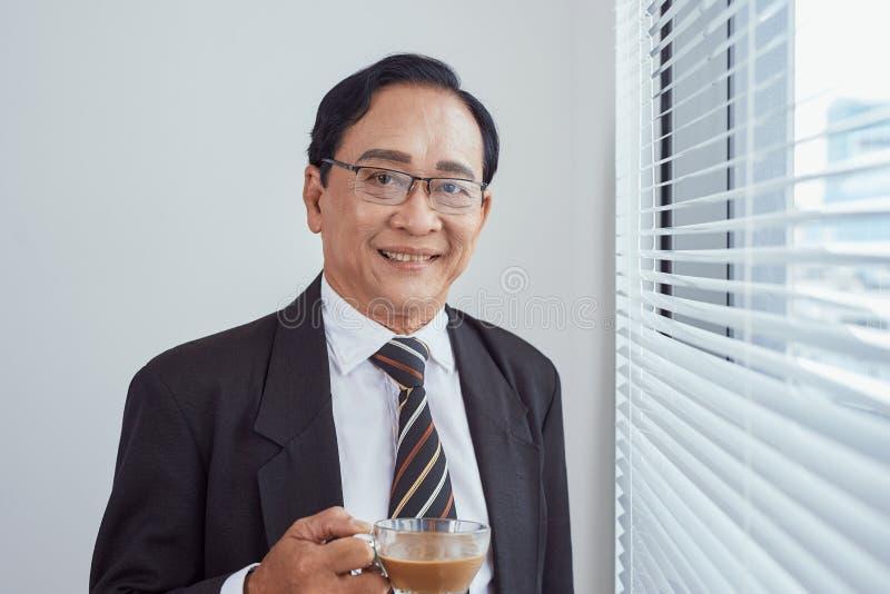 Glimlachende aantrekkelijke rijpe mens die glazen dragen die op de vensterbank van een groot helder venster met exemplaar het rui royalty-vrije stock foto