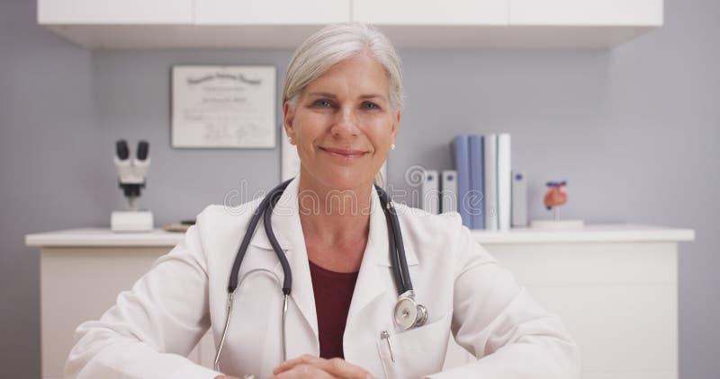 Glimlachende aantrekkelijke rijpe vrouwelijke arts die aan camera geduldig POV spreken stock afbeeldingen