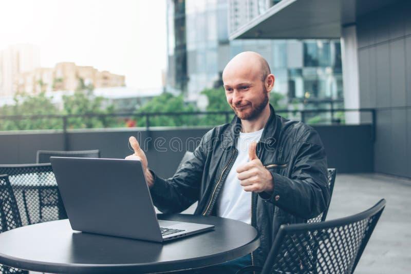 Glimlachende aantrekkelijke volwassen succesvolle kale gebaarde mens in zwart jasje met laptop in straatkoffie bij stad stock fotografie
