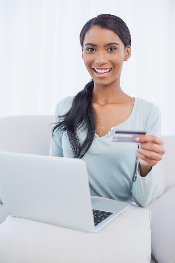 Glimlachende aantrekkelijke vrouw die haar laptop met behulp van online te kopen royalty-vrije stock afbeeldingen