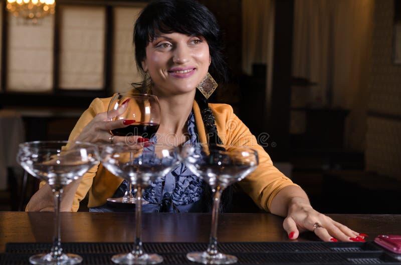 Glimlachende aantrekkelijke vrouw die van een drank geniet stock fotografie