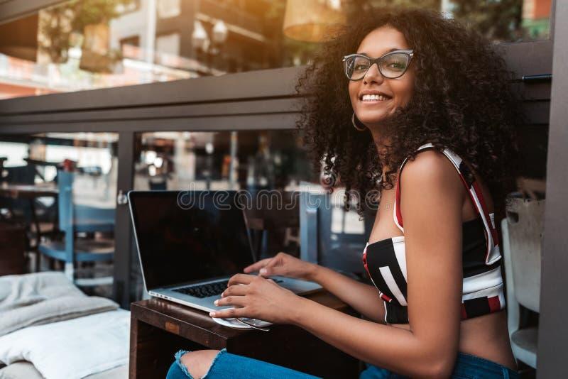 Glimlachende Afrikaans-Amerikaanse vrouwelijke werkgever in oogglazen met laptop in een openluchtkoffie; vrolijke Braziliaanse on royalty-vrije stock afbeeldingen