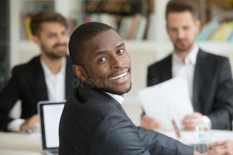 Glimlachende Afrikaanse Amerikaan die camera terug over schouder bekijken stock foto's