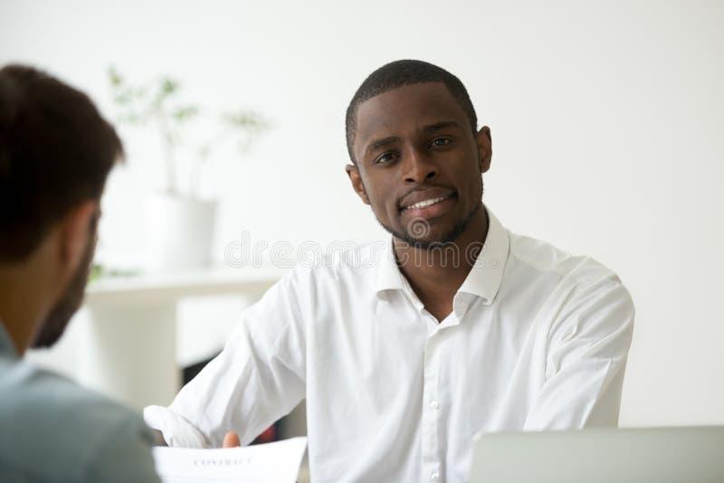 Glimlachende Afrikaanse Amerikaanse arbeider die camera in bureau bekijken stock afbeeldingen