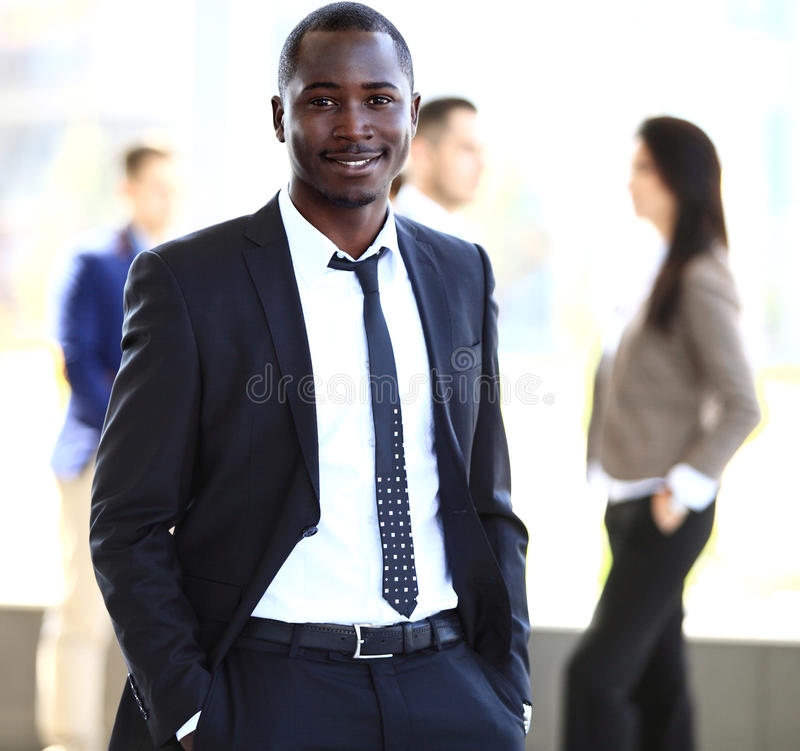 Glimlachende Afrikaanse Amerikaanse bedrijfsmens met stafmedewerkers die op achtergrond werken stock foto