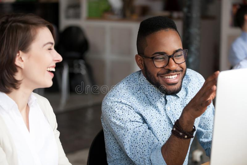 Glimlachende Afrikaanse Amerikaanse mens die met vrouwelijke collega spreken stock afbeeldingen