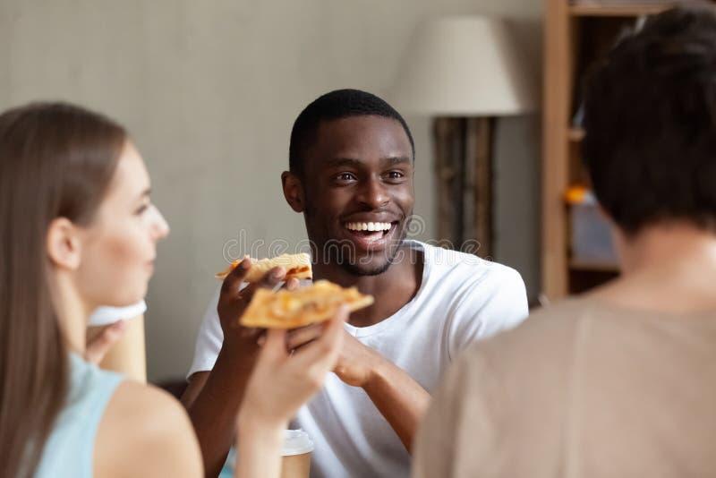 Glimlachende Afrikaanse Amerikaanse mens die pizza eten, die met vrienden babbelen stock fotografie