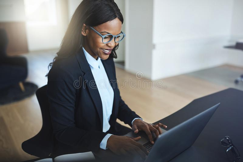 Glimlachende Afrikaanse Amerikaanse onderneemster die in haar bureau werken royalty-vrije stock afbeelding