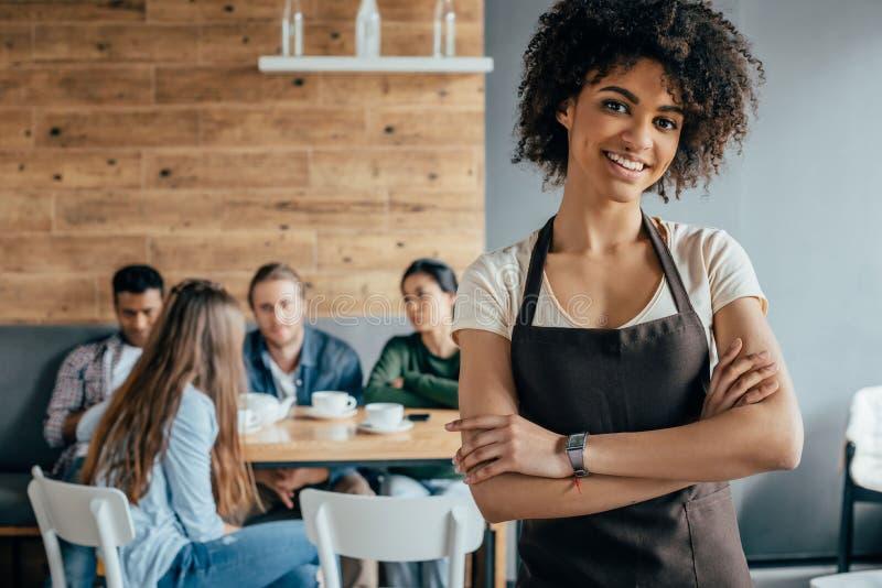 Glimlachende Afrikaanse Amerikaanse serveerster die zich met klanten bevinden die erachter zitten royalty-vrije stock foto's