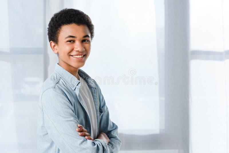 glimlachende Afrikaanse Amerikaanse tiener die zich met gekruiste wapens bevinden en camera bekijken royalty-vrije stock foto