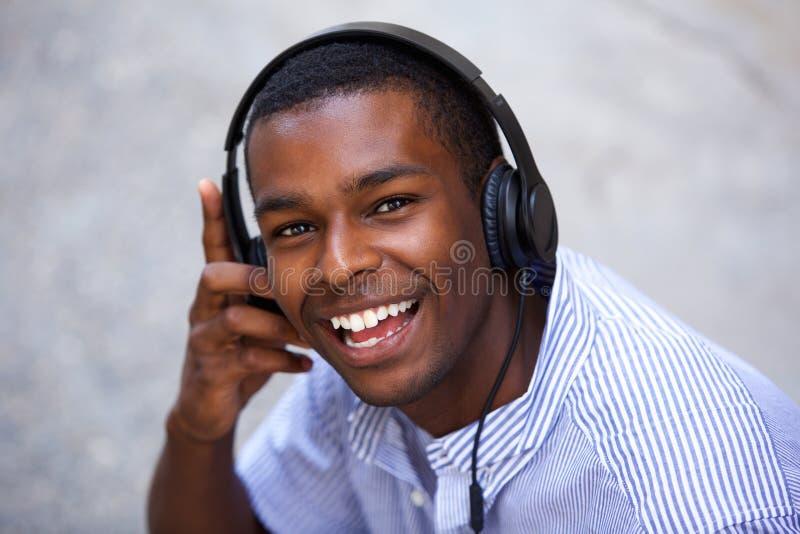 Glimlachende Afrikaanse Amerikaanse tiener met hoofdtelefoons stock afbeeldingen