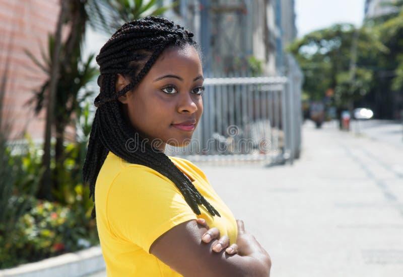 Glimlachende Afrikaanse Amerikaanse vrouw die in geel overhemd zijdelings kijken stock afbeeldingen