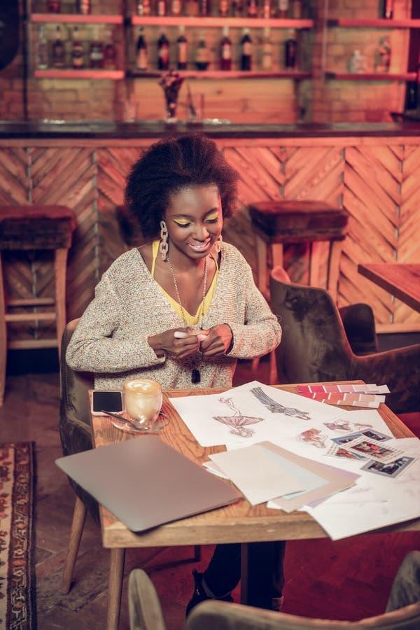Glimlachende Afrikaanse dame die de tekeningszitting van het manierontwerp in cafetaria doen stock fotografie