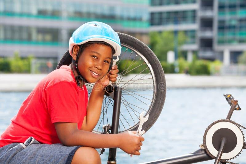 Glimlachende Afrikaanse jongen die zijn fiets in openlucht herstellen stock foto