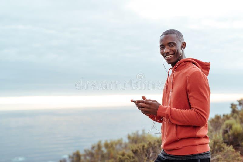 Glimlachende Afrikaanse mens die aan muziek vóór een looppas luisteren stock foto's