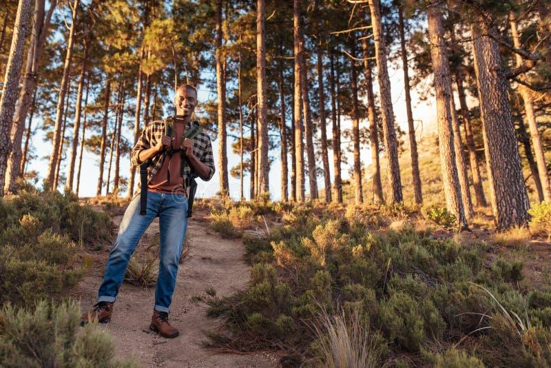 Glimlachende Afrikaanse mens die zich op een sleep in het bos bevinden royalty-vrije stock foto
